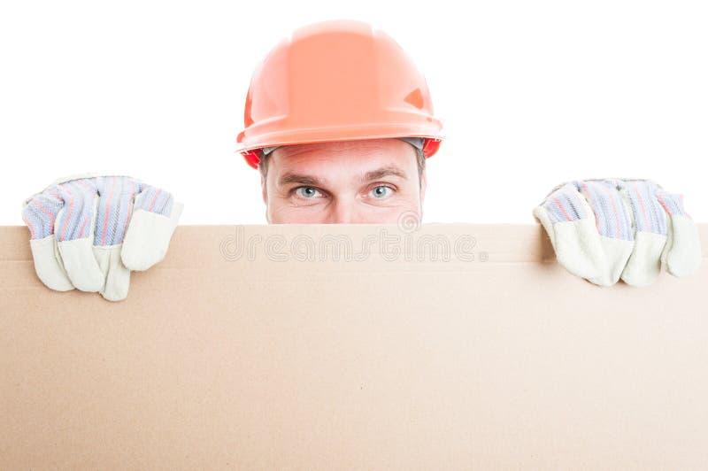Mannelijk aannemers verbergend behing leeg aanplakbord stock foto's