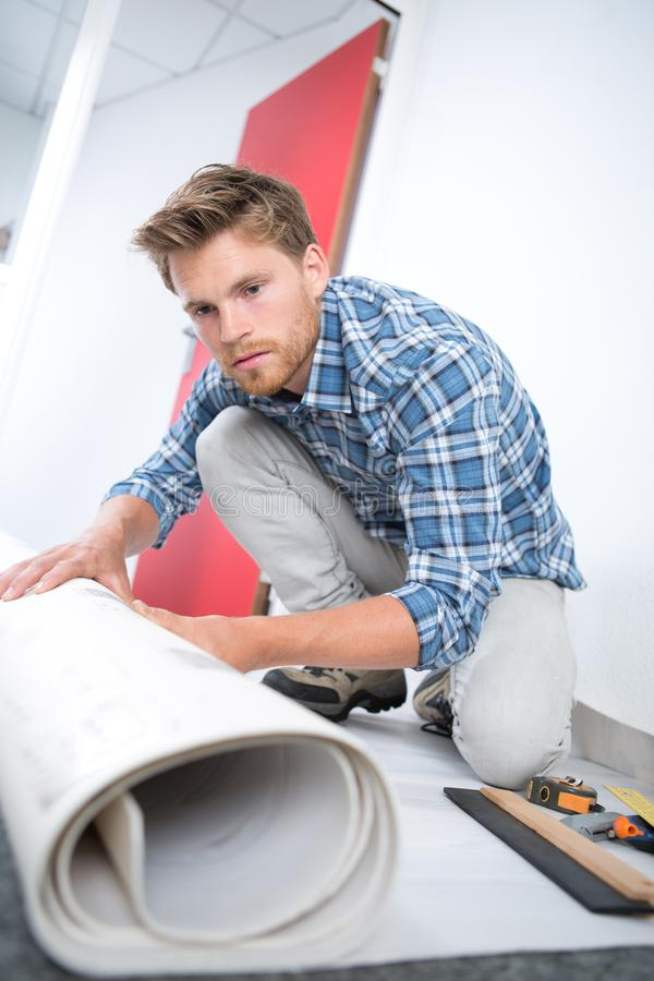Mannelijk Arbeiders Uitrollend Tapijt op Vloer thuis stock afbeeldingen
