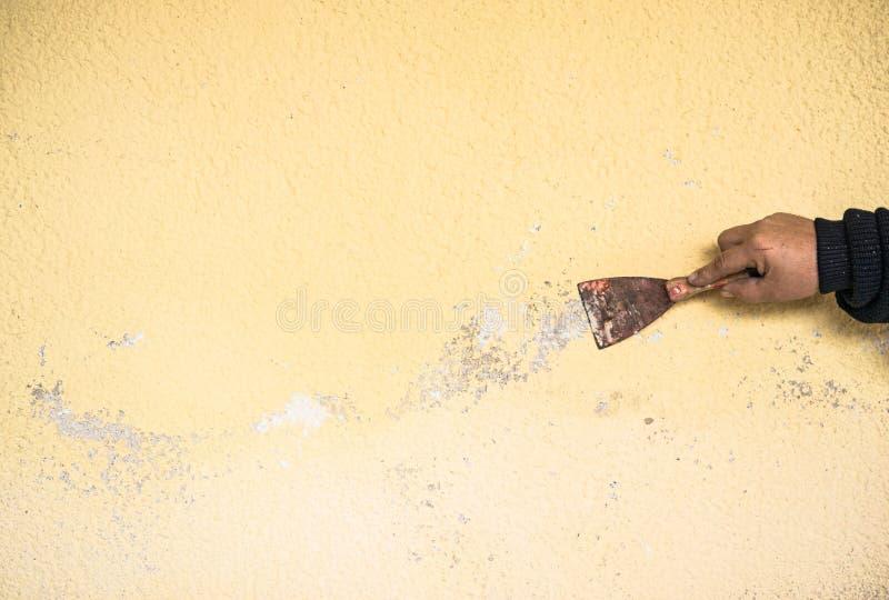 Mannelijk arbeiderswapen met spatel die oud pleister van muur krassen stock foto