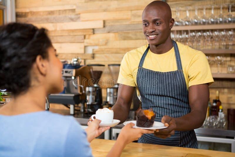 Mannelijk barista dienend koffie en dessert aan vrouwelijke klant royalty-vrije stock foto's
