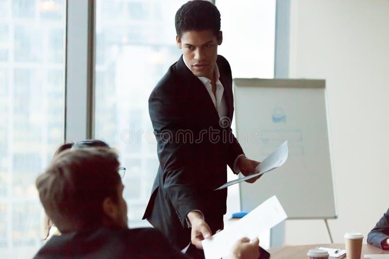 Mannelijk de foldermateriaal van het werknemersaandeel aan collega's op vergadering royalty-vrije stock afbeeldingen
