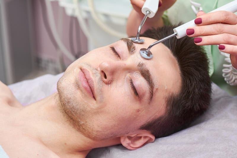 Mannelijk gezicht, microcurrent behandeling stock foto