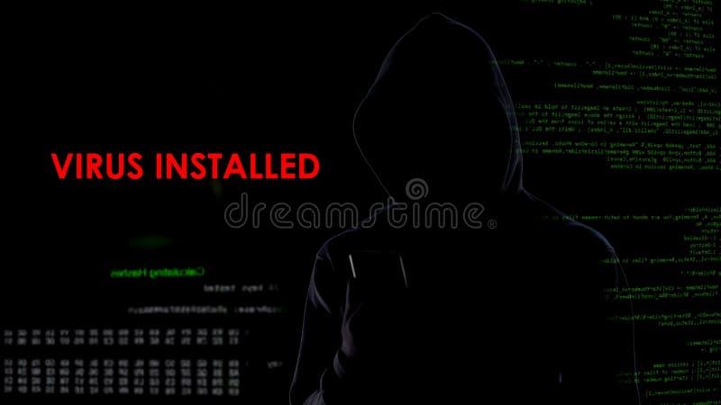 Mannelijk hakker geïnstalleerd virus op vijandelijke laptop, kwaadwillig softwarecomputerprogramma stock afbeeldingen