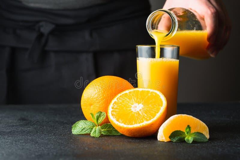 Mannelijk hand gietend jus d'orange in een glas royalty-vrije stock afbeelding