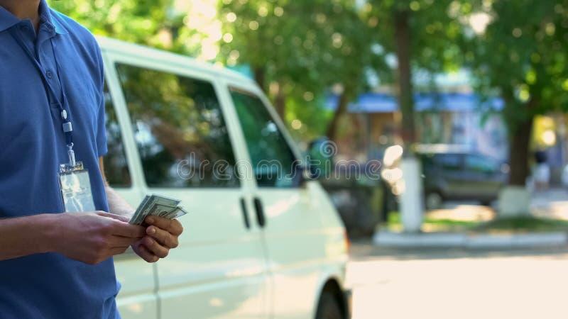Mannelijk koeriers tellend die geld voor pakketlevering wordt ontvangen, de betalingsdienst per uur royalty-vrije stock foto's