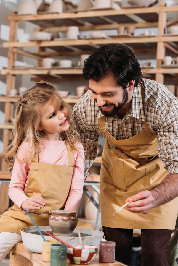 mannelijk leraar en kind die ceramische pot schilderen royalty-vrije stock foto