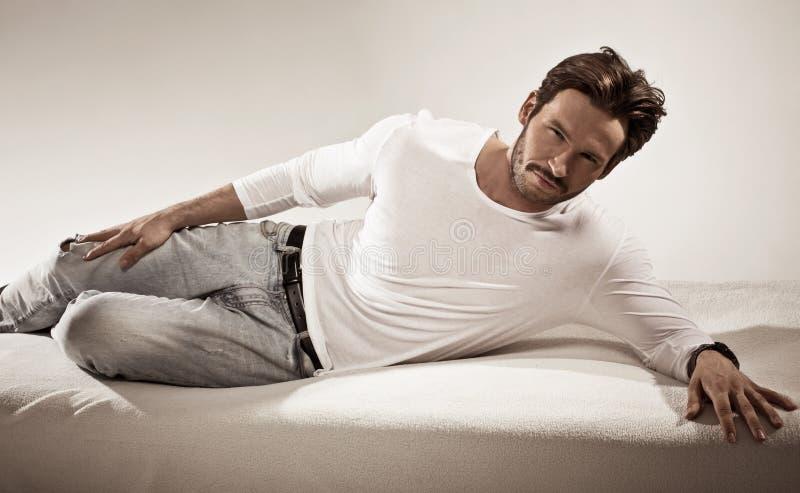 Mannelijk model die op bed liggen stock afbeeldingen