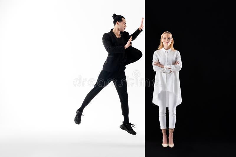 Mannelijk model zwart kostuum dragen en vrouwelijk model die in het witte stellen royalty-vrije stock foto