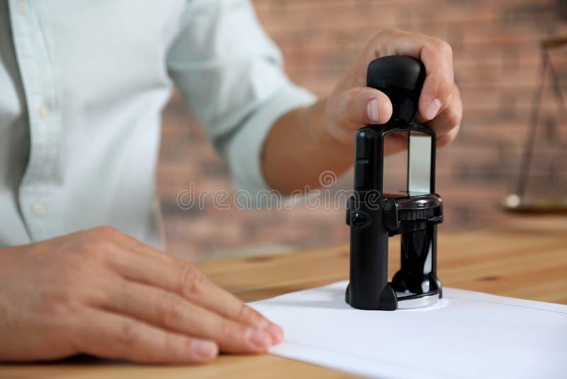 Mannelijk notaris het stempelen document bij lijst stock afbeeldingen