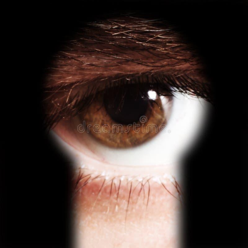 Mannelijk oog die door een sleutelgat spioneren stock afbeelding
