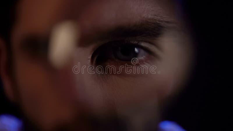 Mannelijk oog die door vergrootglasclose-up kijken, moordenaar na slachtoffer royalty-vrije stock foto