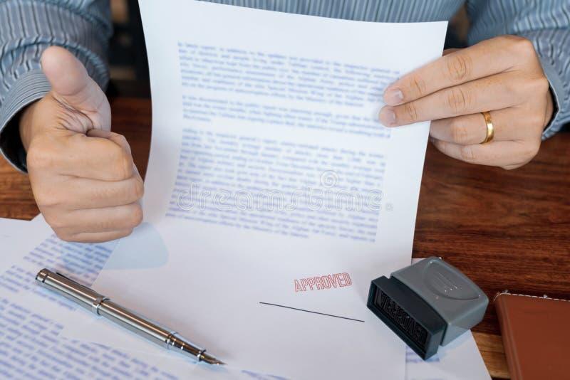 Mannelijk punt aan het ondertekenen van bedrijfsdocument voor het zetten van handtekening, vulpen en goedgekeurd gestempeld op ee royalty-vrije stock fotografie