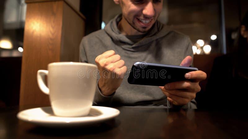 Mannelijk speelspel op smartphone in koffie, winnaar die ja gebaar, verslaving tonen royalty-vrije stock foto's