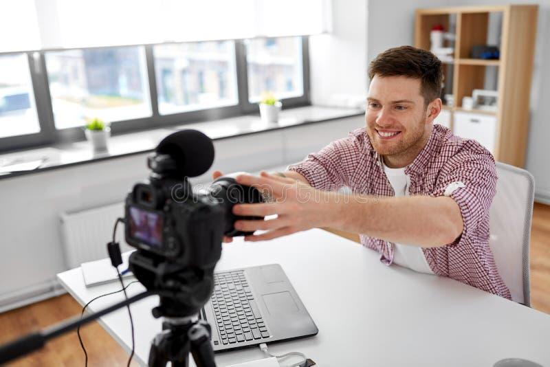 Mannelijk videoblogger het aanpassen camera thuis bureau stock afbeelding