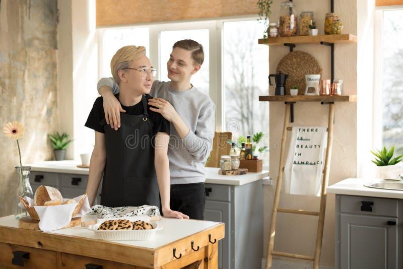 Mannelijk vrolijk paar die elkaar in de ochtend in de keuken thuis koesteren stock foto