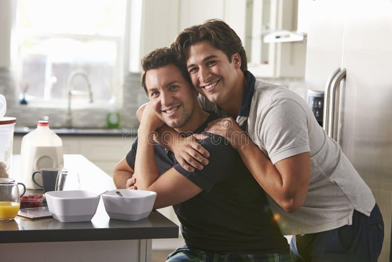 Mannelijk vrolijk paar die in hun keuken, zijaanzicht omhelzen stock foto's