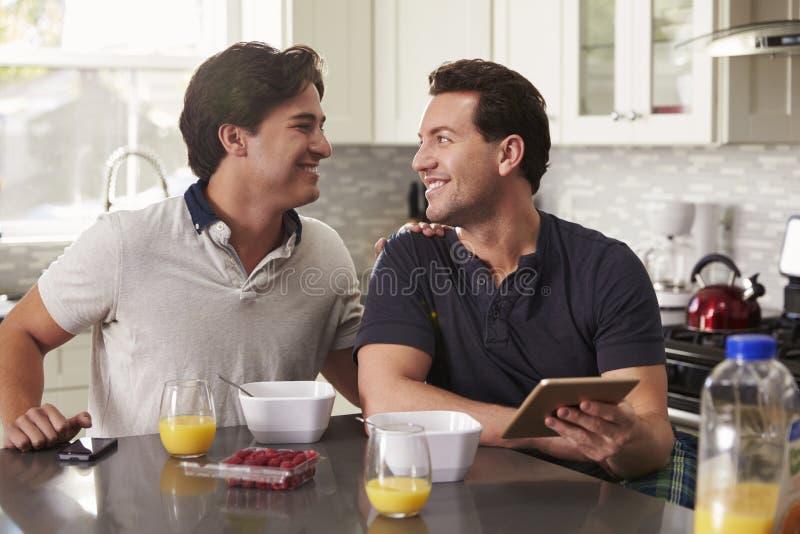 Mannelijk vrolijk paar die in keuken met tablet elkaar bekijken stock fotografie
