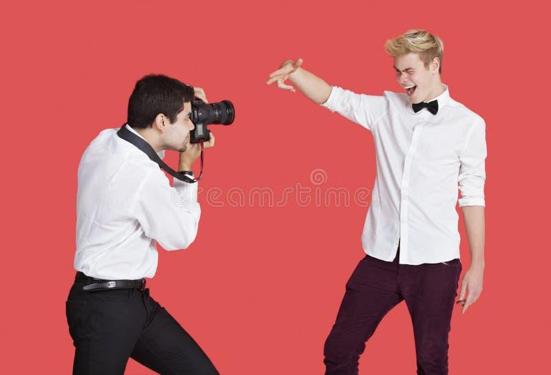 Mannelijke acteur die door paparazzi over rode achtergrond worden gefotografeerd royalty-vrije stock afbeeldingen
