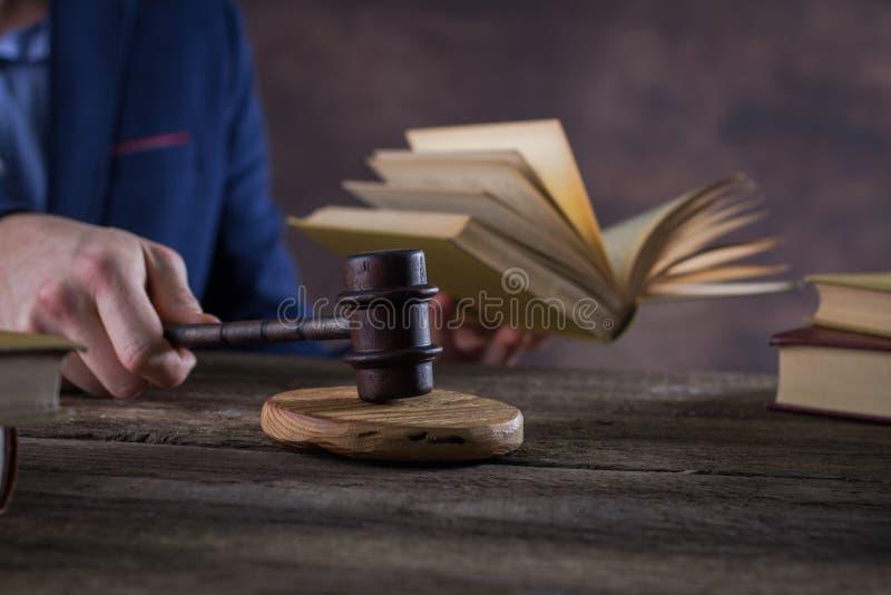 Mannelijke advocaat of rechter die met contractdocumenten, Wetsboeken en houten hamer aan lijst in rechtszaal werken, stock foto's