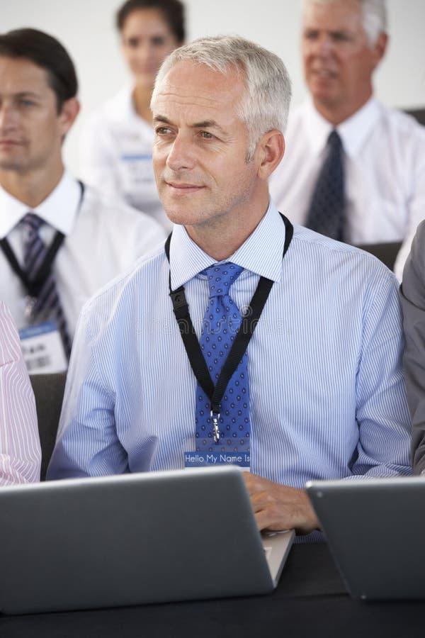 Mannelijke Afgevaardigde die aan Presentatie op Conferentie luisteren die Nota's over Laptop maken stock foto