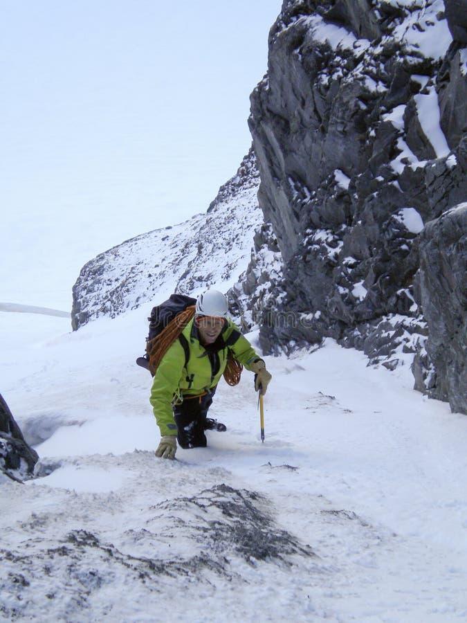 Mannelijke alpinistrubriek omhoog een steile sneeuwgeul en couloir vroeg in de ochtend op zijn manier aan een hoge alpiene piek i stock afbeelding