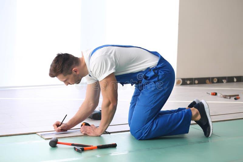 Mannelijke arbeider die bevloering installeren stock afbeelding