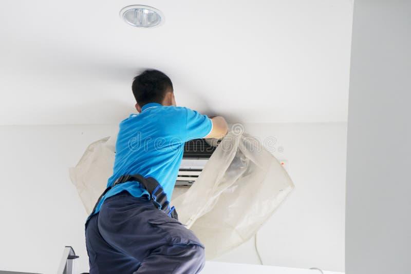 Mannelijke arbeider die een airconditioner van stof schoonmaken royalty-vrije stock afbeelding