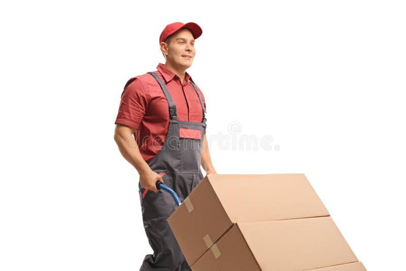 Mannelijke arbeider die een handvrachtwagen met dozen duwen stock foto
