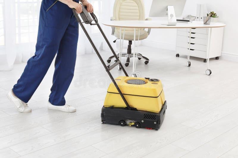 Mannelijke arbeider met vloer schoonmakende machine stock fotografie