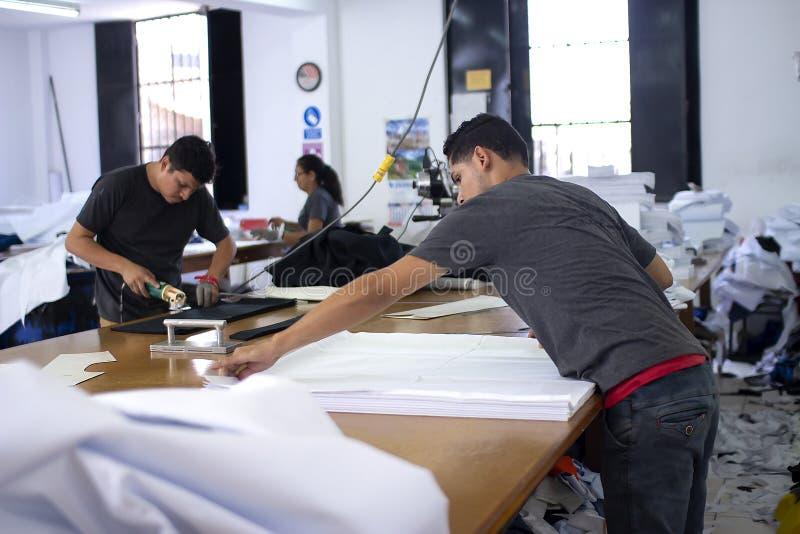 Mannelijke arbeider op een het naaien vervaardiging die stoffen vouwen en elektrische scherpe stoffenmachine met kettingshandscho royalty-vrije stock afbeelding