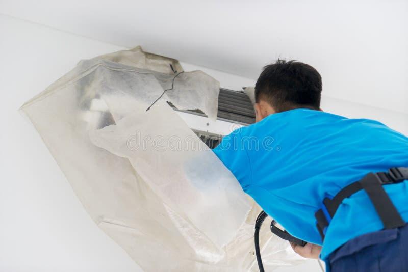 Mannelijke arbeider washs een airconditioner van stof stock fotografie
