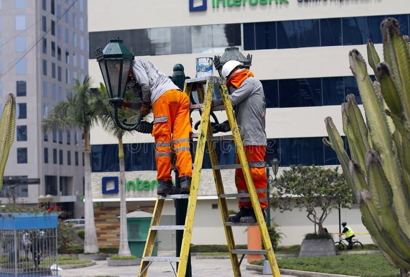 Mannelijke arbeiders die het onderhoudswerk voor de gemeente in parken doen stock afbeelding