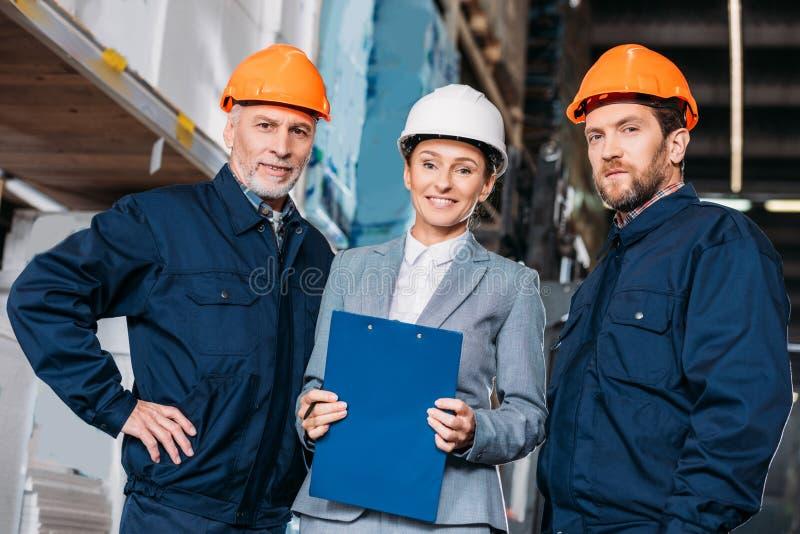 mannelijke arbeiders en vrouwelijke inspecteur in helmen royalty-vrije stock fotografie