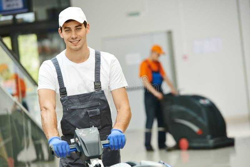 Mannelijke arbeiders schoonmakende bedrijfszaal royalty-vrije stock afbeeldingen