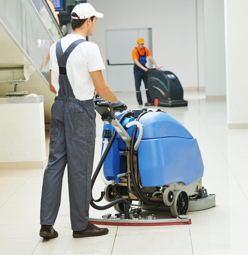 Mannelijke arbeiders schoonmakende bedrijfszaal royalty-vrije stock foto
