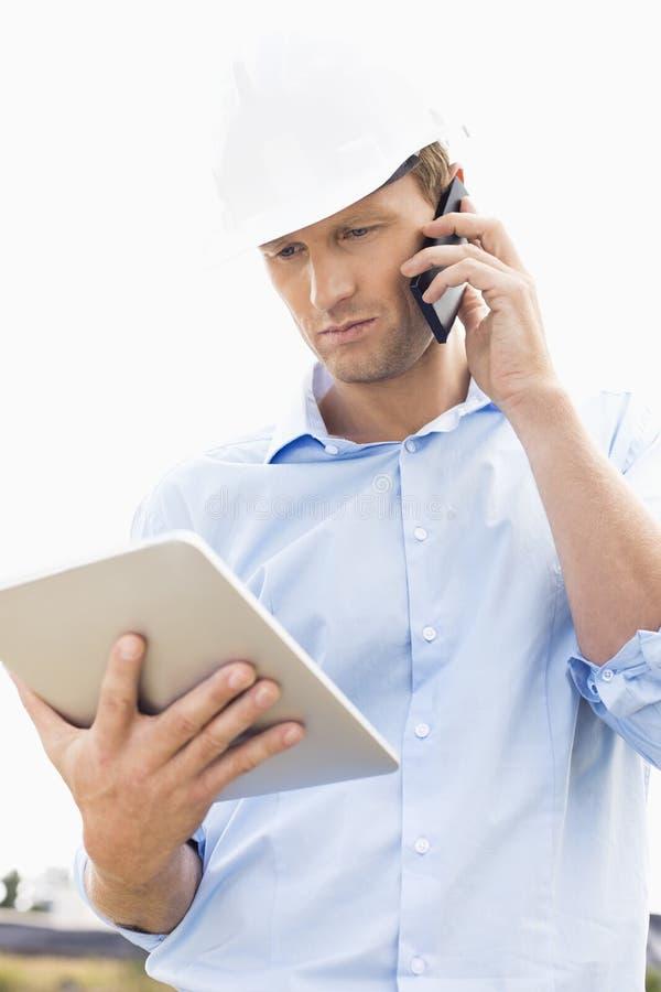 Mannelijke architect met digitale tablet die celtelefoon met behulp van bij plaats stock foto's