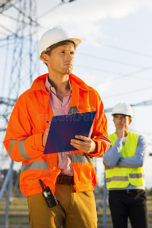 Mannelijke architect met klembord die bij plaats werken terwijl medewerker die zich op achtergrond bevinden stock foto