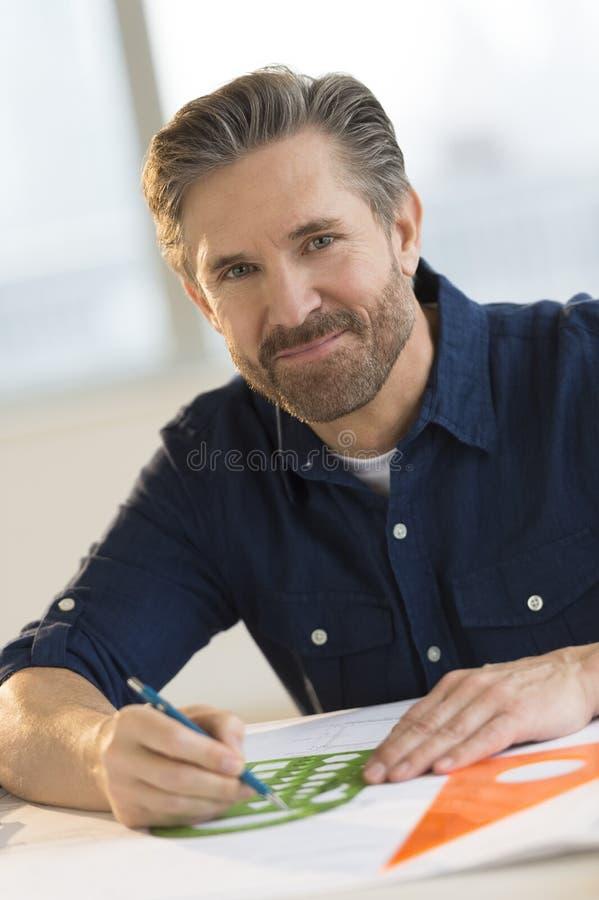 Mannelijke Architect Working On Blueprint bij Bureau stock foto's