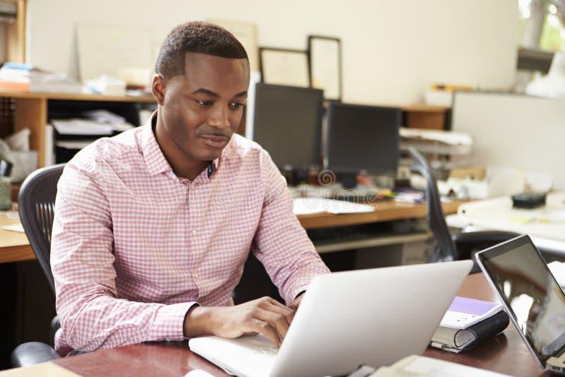 Mannelijke Architect Working At Desk op Laptop stock foto's