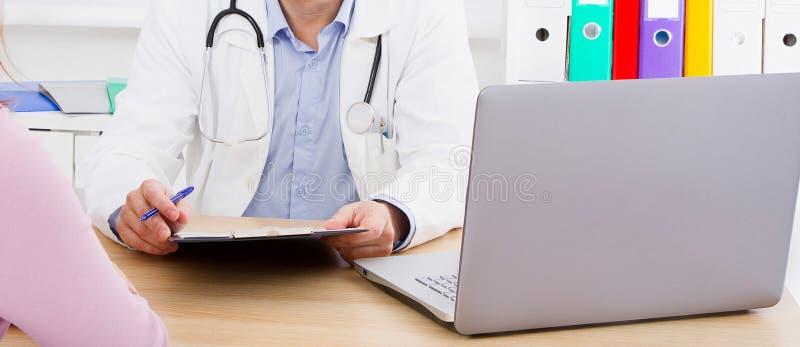 Mannelijke arts bij de lijst die aandachtig aan geduldige klachten luisteren stock afbeelding