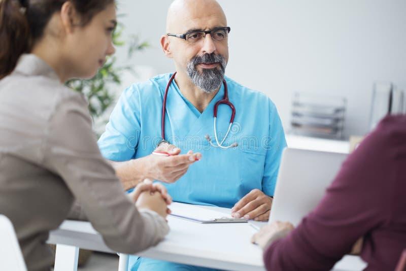 Mannelijke arts die aan jong paar spreken stock afbeelding