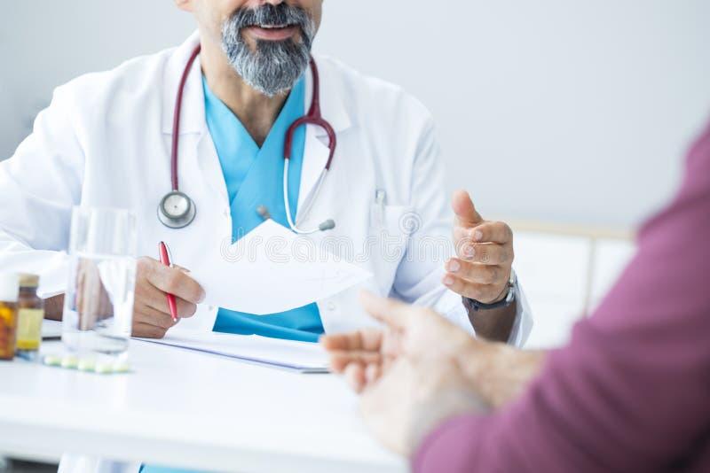 Mannelijke arts die aan patiënt spreken stock foto's