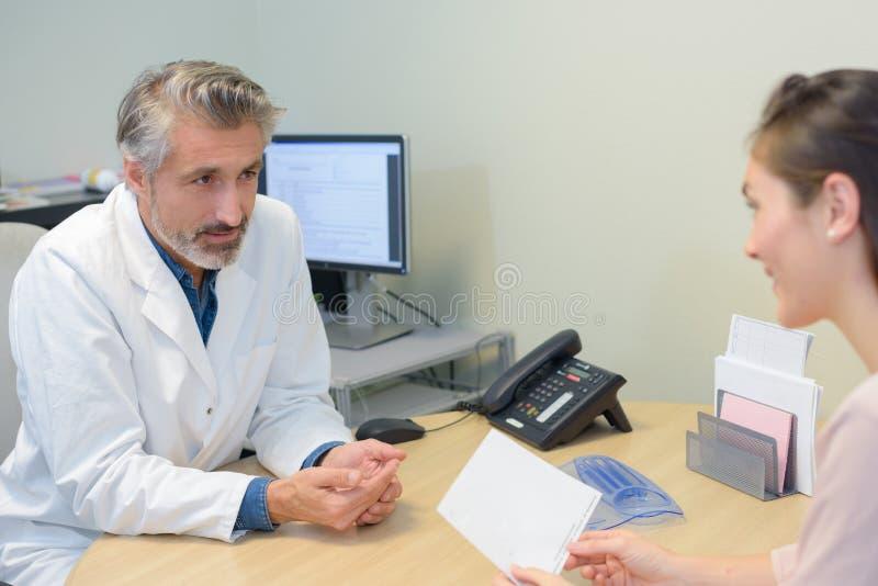 Mannelijke arts die aan vrouwelijke patiënt spreken stock fotografie