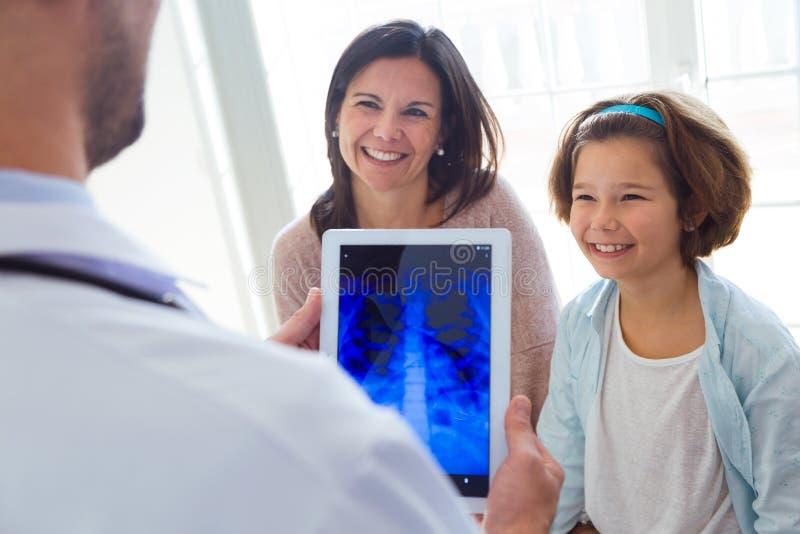 Mannelijke arts die de borstradiografie van het meisje in het bureau raadplegen royalty-vrije stock foto's