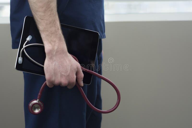 Mannelijke arts die een tablet voor medische informatie houden royalty-vrije stock fotografie