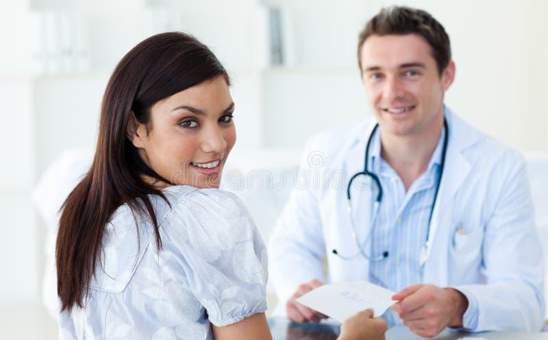 Mannelijke arts die een voorschrift geeft aan zijn patiënt stock foto