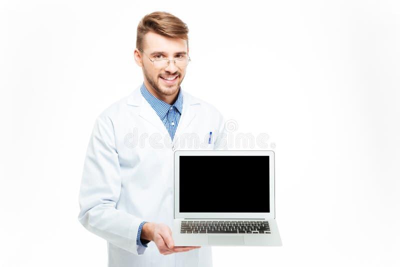 Mannelijke arts die het lege laptop computerscherm tonen stock afbeelding