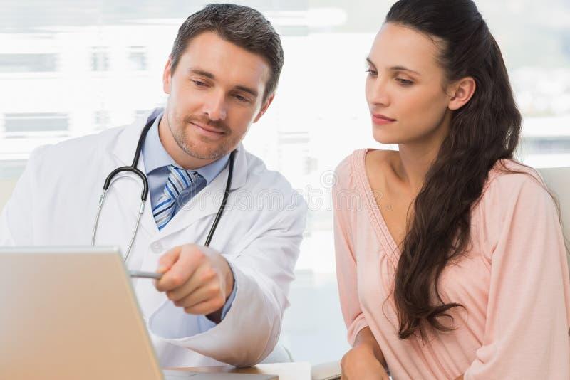 Mannelijke arts die iets op laptop tonen aan patiënt stock afbeeldingen