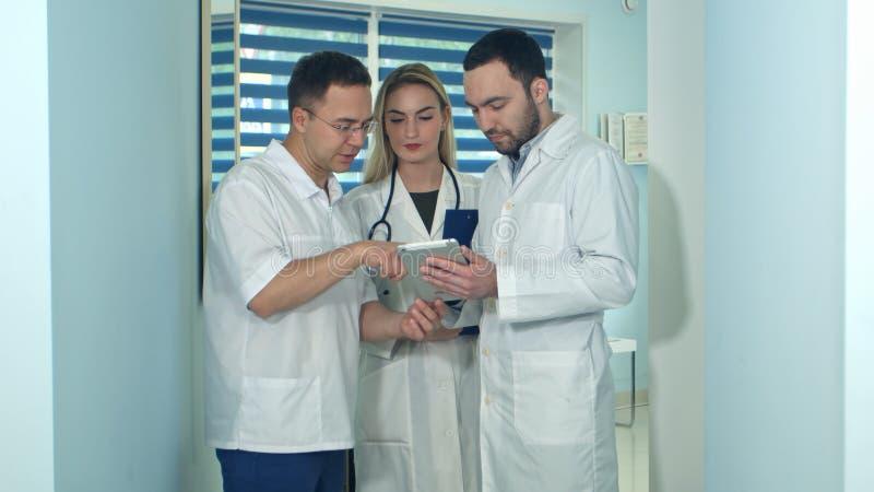 Mannelijke arts die iets op tablet tonen aan zijn collega's stock afbeelding