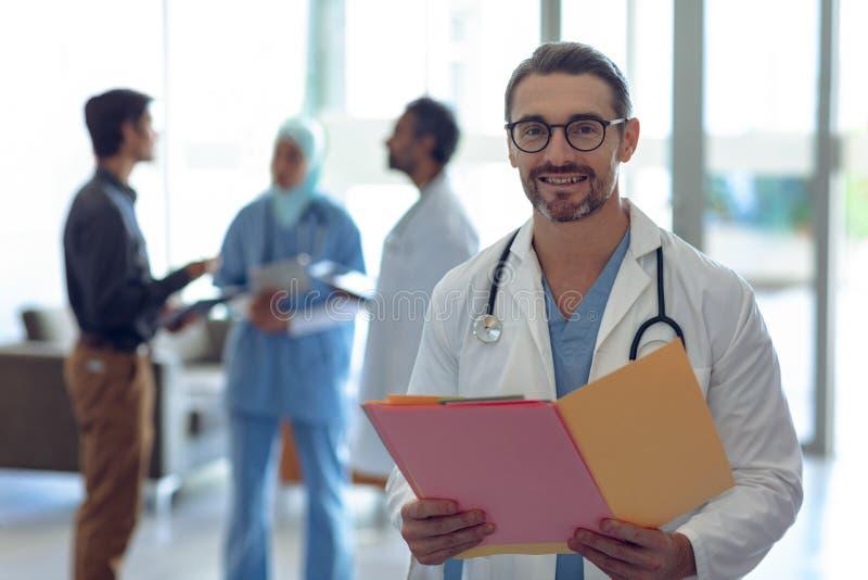 Mannelijke arts die medisch dossier houden en camera in het ziekenhuis bekijken stock afbeeldingen